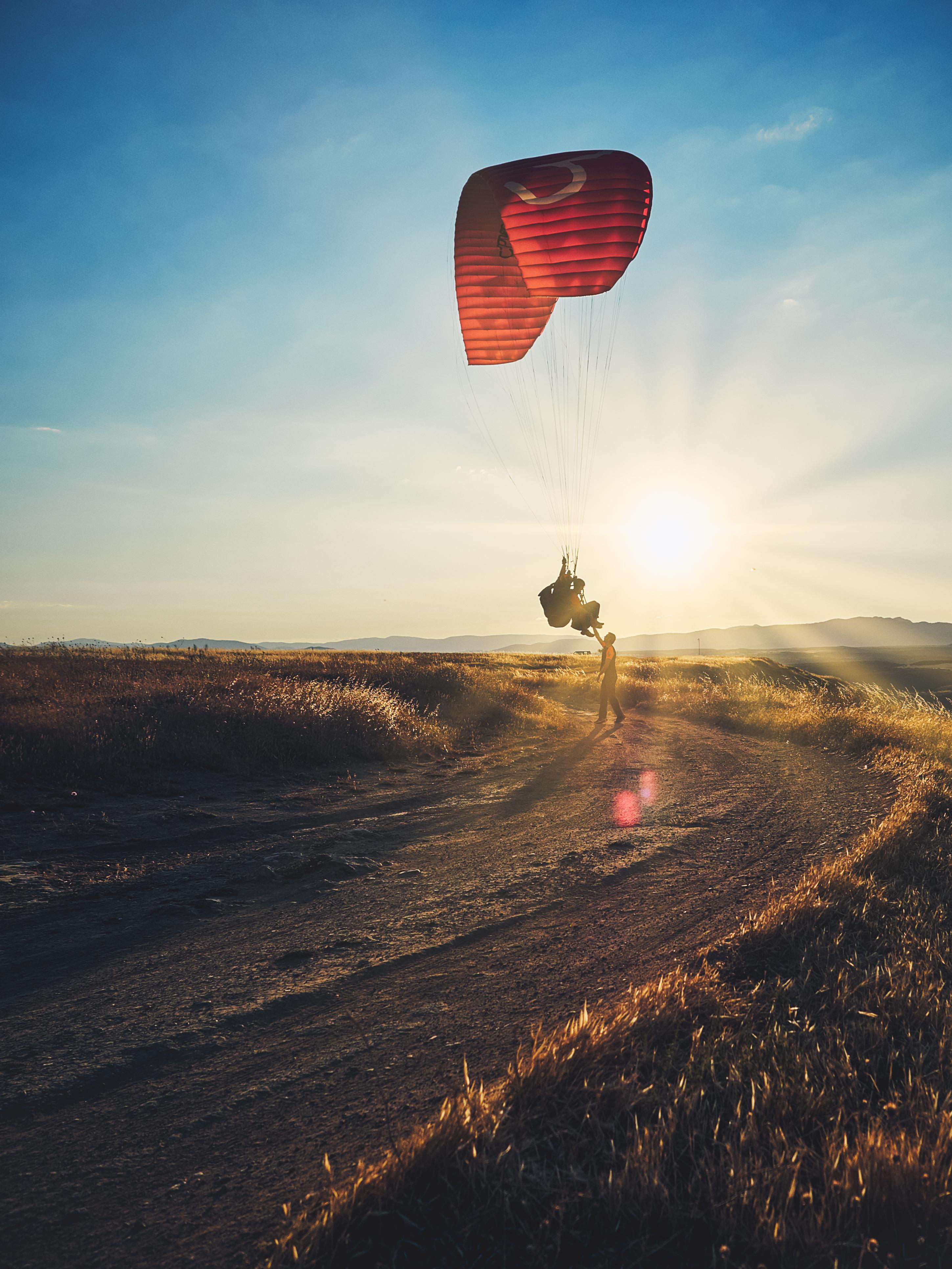 Parapente volando en la puesta de sol